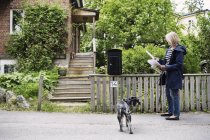 Senior woman checking letters while standing with dog outside house — Stock Photo