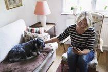 Femme âgée utilisant un téléphone intelligent tout en caressant chien relaxant sur le canapé à la maison — Photo de stock