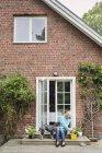 Femme âgée avec chien assis à l'entrée de la maison — Photo de stock
