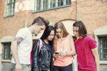 Amigos de la escuela secundaria leyendo mensaje de texto en el teléfono móvil en el patio de la escuela - foto de stock