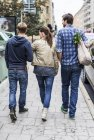 Rear view of friends walking together on sidewalk — Stock Photo