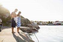 Piena lunghezza di giovane coppia avvolto in asciugamani in piedi in riva al lago — Foto stock