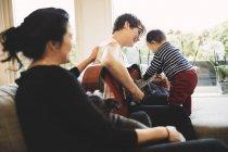 Mulher que olha a matriz e a filha de sorriso que jogam a guitarra em casa — Fotografia de Stock