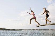 Toute la longueur du jeune couple, plongée dans le lac contre ciel nuageux — Photo de stock