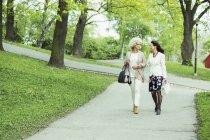 Lunghezza completa delle donne anziane che camminano sul sentiero del giardino — Foto stock