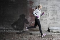 Full length of woman jogging on street — Stock Photo