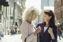 Senior female friends talking on city street — Stock Photo