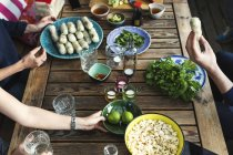 Cropped image of friends having food at table in log cabin — Stock Photo
