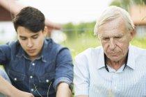 Pensativo homem sênior com neto sentado no quintal — Fotografia de Stock