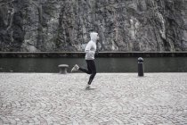 Man jogging on street against rock — Stock Photo