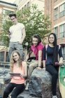 Portrait of smiling high school students sitting on rock at schoolyard — Stock Photo
