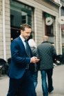 Mature businessman using smart phone while walking on sidewalk in city — Stock Photo