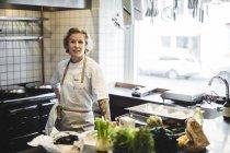 Retrato do proprietário fêmea confiável que está pelo contador de cozinha no restaurante — Fotografia de Stock