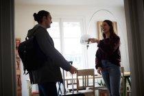 Lächelnde Frau mit Schlüsseln im Gespräch mit Mann in Wohnung an sonnigem Tag — Stockfoto