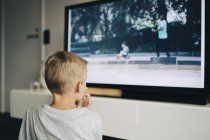 Rear view of boy watching smart TV in living room at home — Stock Photo