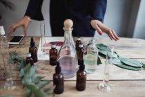 Mittelteil der Mitte adult Unternehmerin Parfüm auf Tabelle am Workshop vorbereiten — Stockfoto
