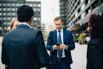 Empresário maduro usando telefone inteligente enquanto está em meio a colegas na cidade — Fotografia de Stock