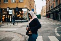 Vista laterale della ragazza adolescente che rimuove il telefono cellulare dalla borsa mentre cammina per strada in città — Foto stock