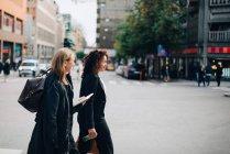 Вид збоку жіночий бізнес колег ходіння по тротуару в місті — стокове фото