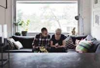 Seniorenpaar sitzt mit Smartphone auf Sofa im Wohnzimmer gegen Fenster — Stockfoto