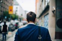Rear view of mature businessman walking on sidewalk in city — Stock Photo