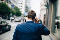 Vista trasera del hombre de negocios maduro hablando por teléfono móvil mientras camina en la acera de la ciudad - foto de stock