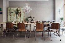 Tavolo in legno in mezzo sedie con bottiglie di profumo contro la parete al workshop — Foto stock