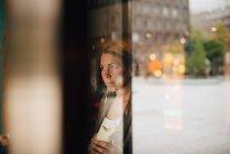 Mulher de negócios maduro comendo sanduíche de envoltório no café visto da janela — Fotografia de Stock