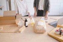 Meio das mulheres empresárias permanente com vários objetos de fabricação na tabela na oficina — Fotografia de Stock
