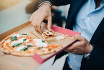 Midsection of businessman eating pizza from cardboard box in city — Stock Photo