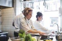 Mujeres chefs preparando comida en mostrador por colegas en la cocina en el restaurante - foto de stock