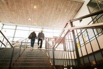Низким углом зрения молодая пара, движущихся по лестнице на станции метро — стоковое фото