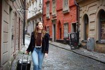 Junge Frau schaut weg, während sie mit Gepäck in Gasse geht — Stockfoto