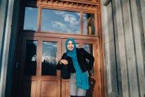 Vista de ángulo bajo de la joven sonriente usando hijab de pie contra la puerta - foto de stock