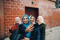 Feliz jovem muçulmana tendo selfie com amigos do sexo feminino na calçada contra edifício cidade — Fotografia de Stock