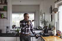 Senior man talking on smart phone through in-ear headphones while standing in kitchen at home — Stock Photo