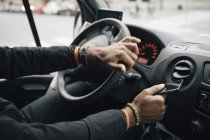 Обітнутого зображення чоловік тримає мобільного телефону під час водіння доставки Ван — стокове фото