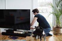 Femme enceinte arrangeant des câbles de télévision tout en s'agenouillant par chien dans le salon — Photo de stock
