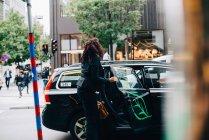 Meados empresária adulta entrar em táxi na rua na cidade — Fotografia de Stock