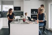 Family in kitchen using technologies at home — Stock Photo
