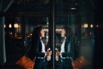 Вид збоку середині дорослий бізнес-леді проведення продукти харчування та напої під час прогулянки в кафе — стокове фото