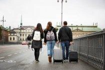 Pleine longueur d'amis marchant avec des bagages sur le pont en ville contre un ciel dégagé — Photo de stock