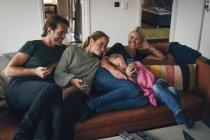 Famille souriante regardant garçon en utilisant un téléphone portable tout en étant assis sur le canapé à la maison — Photo de stock
