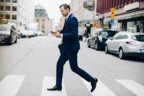 Visão lateral de comprimento total de empresário maduro cruzando rua enquanto usa telefone inteligente na cidade — Fotografia de Stock