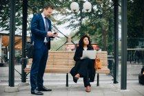Повна довжина ділових людей, використовуючи смарт-телефонами під час очікування на автобусній зупинці — стокове фото