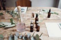Vue d'angle élevé de différentes bouteilles de parfum parmi les feuilles et les brochures sur table — Photo de stock