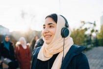 Heureuse adolescente écoutant écouteurs regardant loin contre le ciel — Photo de stock