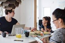 Mère avec ordinateur portable parlant à la fille tandis que femme en utilisant téléphone sur la table à manger — Photo de stock
