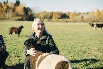 Smiling mature female farmer embracing sheep on field — Stock Photo
