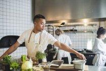 Joven chef masculino cocinando en la cocina contra colegas que trabajan en el restaurante - foto de stock